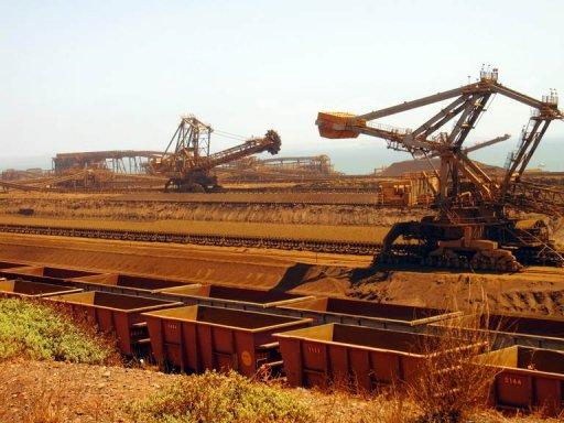 File photo of remote-controlled stackers and reclaimers moving iron ore to rail cars at Rio Tinto's Port Dampier operations in Western Australia's Pilbara region. Iron ore, mostly from the Pilbara region in Western Australia, currently represents nearly 80 percent of the company's earnings