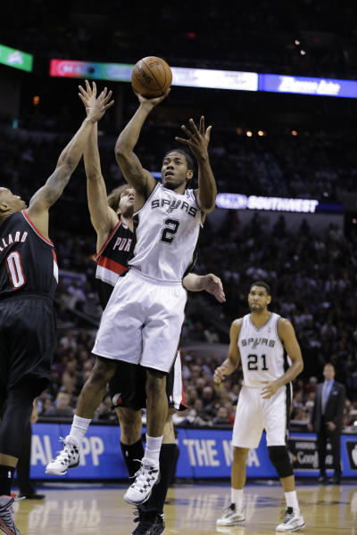 San Antonio Spurs' Kawhi Leonard (2) shoots over Portland Trail Blazers' Damian Lillard (0) and Robin Lopez (42) during the first half of Game 2 of a Western Conference semifinal NBA basketball playoff series, Thursday, May 8, 2014, in San Antonio. (AP Photo/Eric Gay)