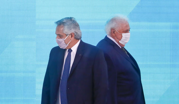 FILE - In this Jan. 14, 2021 file photo, Argentine President Alberto Fernandez, left, walks past Health Minister Gines Gonzalez Garcia as they arrive to a law signing ceremony, in Buenos Aires, Argentina. Fernandez asked his Gonzalez García to resign on Friday, Jan. 19, 2021, who is alleged to be involved in a scandal over discretionary handling of COVID-19 vaccines. (AP Photo/Marcos Brindicci, File)