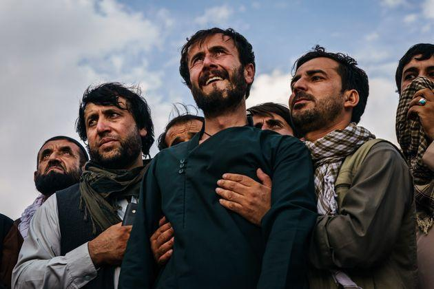 Ramal Ahmadi, center, is supported by family members as he weeps looking up at jet fighters circling above at the conclusion of the U.S. withdrawal. The family was attending a funeral Monday for the 10 people the family said were killed in a U.S. drone strike. (Photo: Marcus Yam/Los Angeles Times via Getty Images)