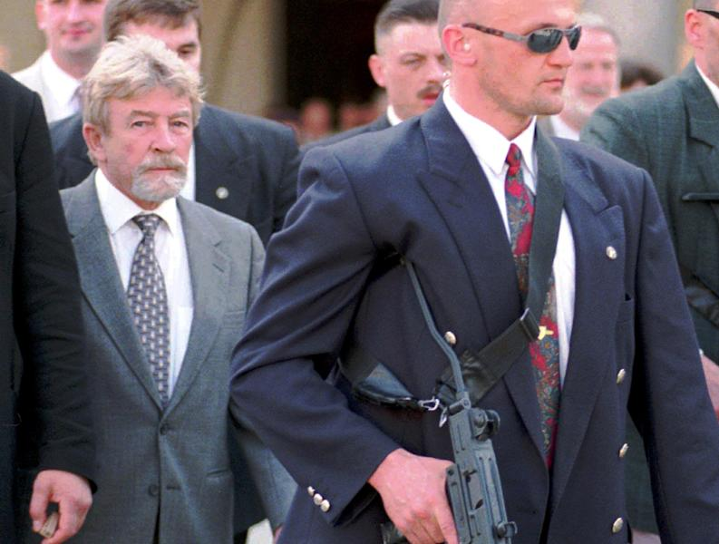 In this file photo of April 30, 1998, surrounded by bodyguards, Poland's Cold War spy, Ryszard Kuklinski, left, visits Krakow, southern Poland. From behind the Iron Curtain, Kuklinski passed some 35,000 pages of Warsaw Pact secrets to the CIA, including the communist government's plan to impose martial law in 1981 and launch a brutal crackdown on the pro-democracy Solidarity movement. He was spirited out of Poland with his wife and two sons shortly before the Dec. 13, 1981 military crackdown, and the family lived in hiding in the U.S. Poland's military court sentenced him to death for treason and desertion. The charges were lifted in 1998 and Kuklinski came on a visit.(AP Photo/Czarek Sokolowski)