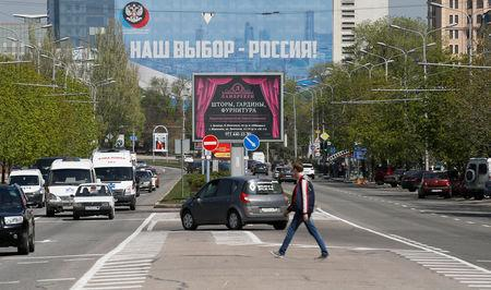 "A banner (top), which reads ""Our choice is Russia!"", is on display in a street in the separatist-controlled city of Donetsk, Ukraine April 25, 2019. REUTERS/Alexander Ermochenko"