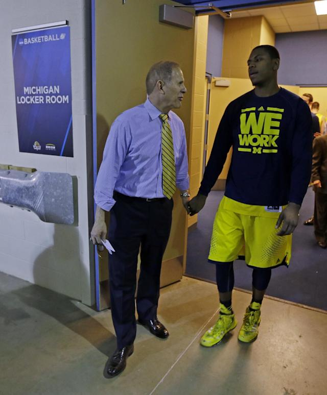 Michigan head coach John Beilein talks to Glenn Robinson III after an NCAA Midwest Regional final college basketball tournament game against Kentucky Sunday, March 30, 2014, in Indianapolis. Kentucky won 75-72 to advance to the Final Four. (AP Photo/Michael Conroy)