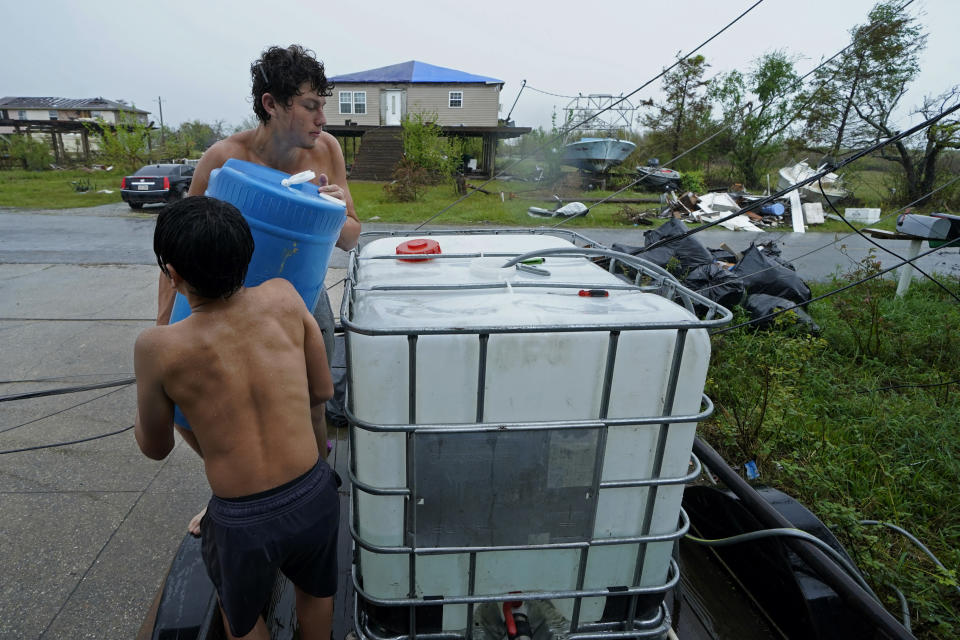 In the aftermath of Hurricane Ida, Terren Dardar, 17, and Dayton Verdin, 14, left, family of Patti Dardar, who works at the marina, pour barrels of rainwater they collected from Tropical Storm Nicholas in Pointe-Aux-Chenes, La., Tuesday, Sept. 14, 2021. They have had no running water since the hurricane, and collected 140 gallons of rainwater in two hours from the tropical storm, which they filter and pump into their house for showers. (AP Photo/Gerald Herbert)
