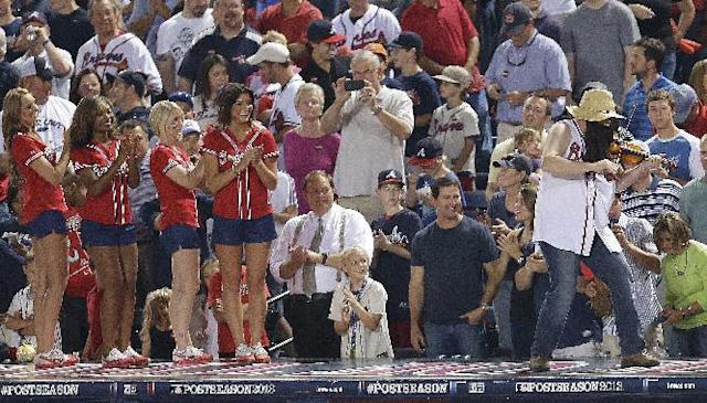 A man plays a fiddle in the sixth inning of Game 2 of the National League division series between the Atlanta Braves and the Los Angeles Dodgers, Friday, Oct. 4, 2013, in Atlanta. (AP Photo/Mike Zarrilli)