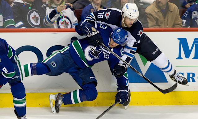 Vancouver Canucks' Kevin Bieksa, left, and Winnipeg Jets' Andrew Ladd collide during the third period of an NHL hockey game in Vancouver, British Columbia, on Sunday, Dec. 22, 2013. (AP Photo/The Canadian Press, Darryl Dyck)