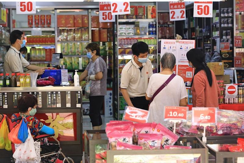 SINGAPORE - MAY 12: People wearing protective masks shop in a store on May 12, 2020 in Singapore. The Singapore government starts easing lockdown measures today to allow businesses such as selected food retail outlets, laundry services, barbers, home-based food businesses and pet supplies stores to resume operations, while still maintaining the partial lockdown until June 1 to bring down the coronavirus (COVID-19) cases within the community. (Photo by Suhaimi Abdullah/Getty Images)