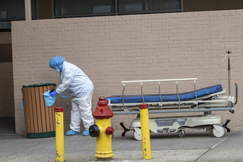 Medical personnel remove their personal protective equipment after delivering a bodies from the Wyckoff Heights Medical Center  to refrigerated containers parked outside,  Thursday, April 2, 2020 in the Brooklyn borough of New York.  As coronavirus hot spots and death tolls flared around the U.S., the nation's biggest city was the hardest hit of the all, with bodies loaded onto refrigerated morgue trucks by gurney and forklift outside overwhelmed hospitals, in full view of passing motorists.   (AP Photo/Mary Altaffer)