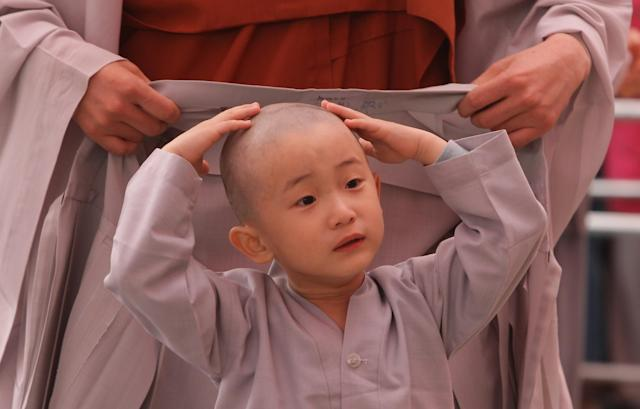 SEOUL, SOUTH KOREA - MAY 03: A child rubs his head after a Buddhist monk shaved his hair off during the 'Children Becoming Buddhist Monks' ceremony forthcoming buddha's birthday at a Chogye temple on May 3, 2013 in Seoul, South Korea. The children will stay at the temple to learn about Buddhism for 14 days. Buddha was born approximately 2,557 years ago, and although the exact date is unknown, Buddha's official birthday is celebrated on the full moon in May in South Korea, which is on May 17 this year. (Photo by Chung Sung-Jun/Getty Images)