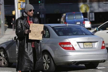 A car drives past a homeless man as he panhandles on the street in New York, January 4, 2016.REUTERS/Lucas Jackson