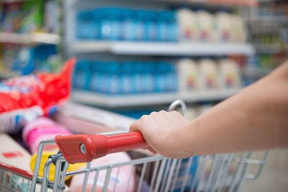 A Customer Pushes A Cart Loaded With A Variety Of Products Through A Grocery  Store Aisle