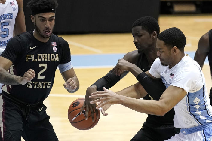 North Carolina forward Garrison Brooks, right, and Florida State center Tanor Ngom struggle for the ball while Florida State guard Anthony Polite (2) looks on during the first half of an NCAA college basketball game in Chapel Hill, N.C., Saturday, Feb. 27, 2021. (AP Photo/Gerry Broome)
