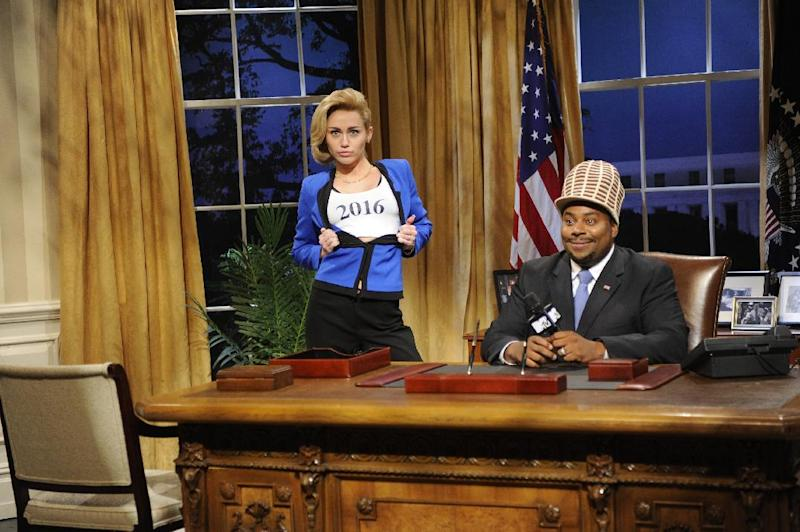 "This Oct. 5, 2013 photo released by NBC shows guest host Miley Cyrus, left, and Kenan Thompson in a scene from the late-night comedy series ""Saturday Night Live,"" in New York. (AP Photo/NBC, Dana Edelson)"