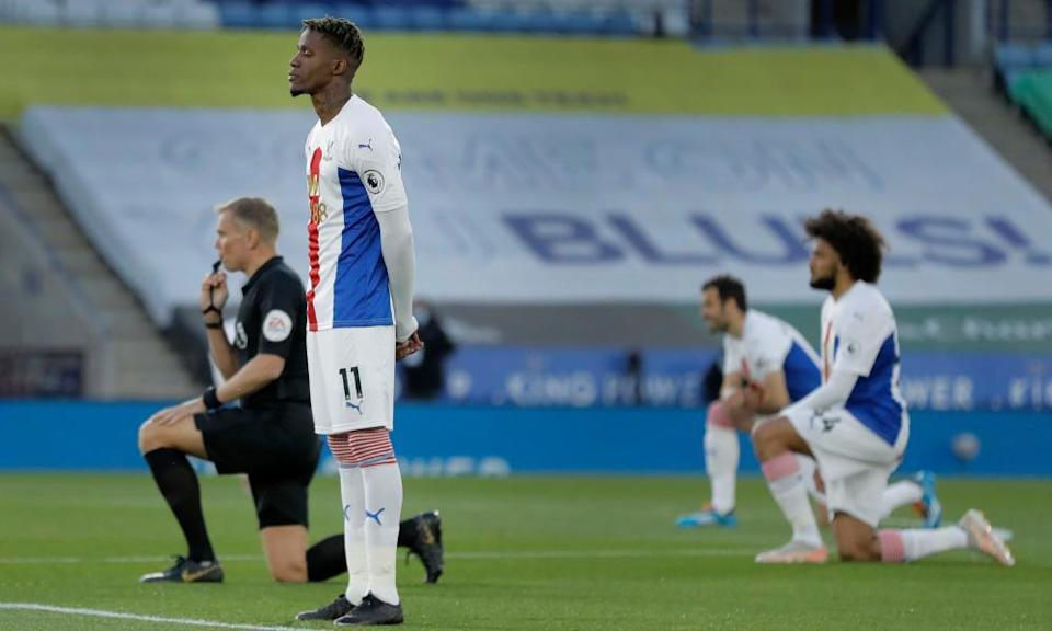 Crystal Palace's Wilfried Zaha stands while others take a knee at Leicester in April. He feels kneeling is not enough of an anti-racist action.