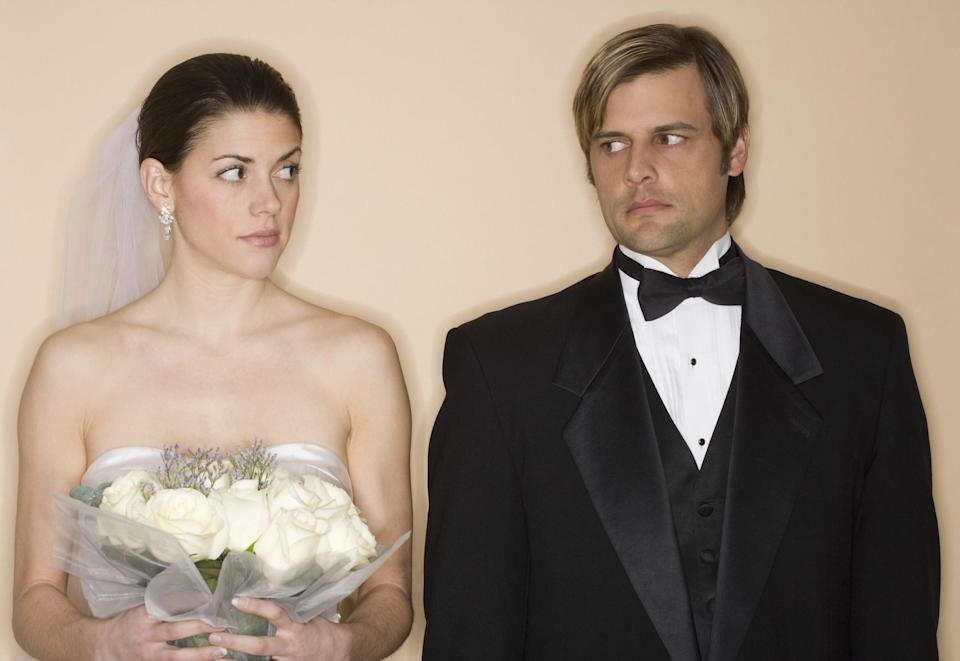A bride and groom eyeing each other suspiciously