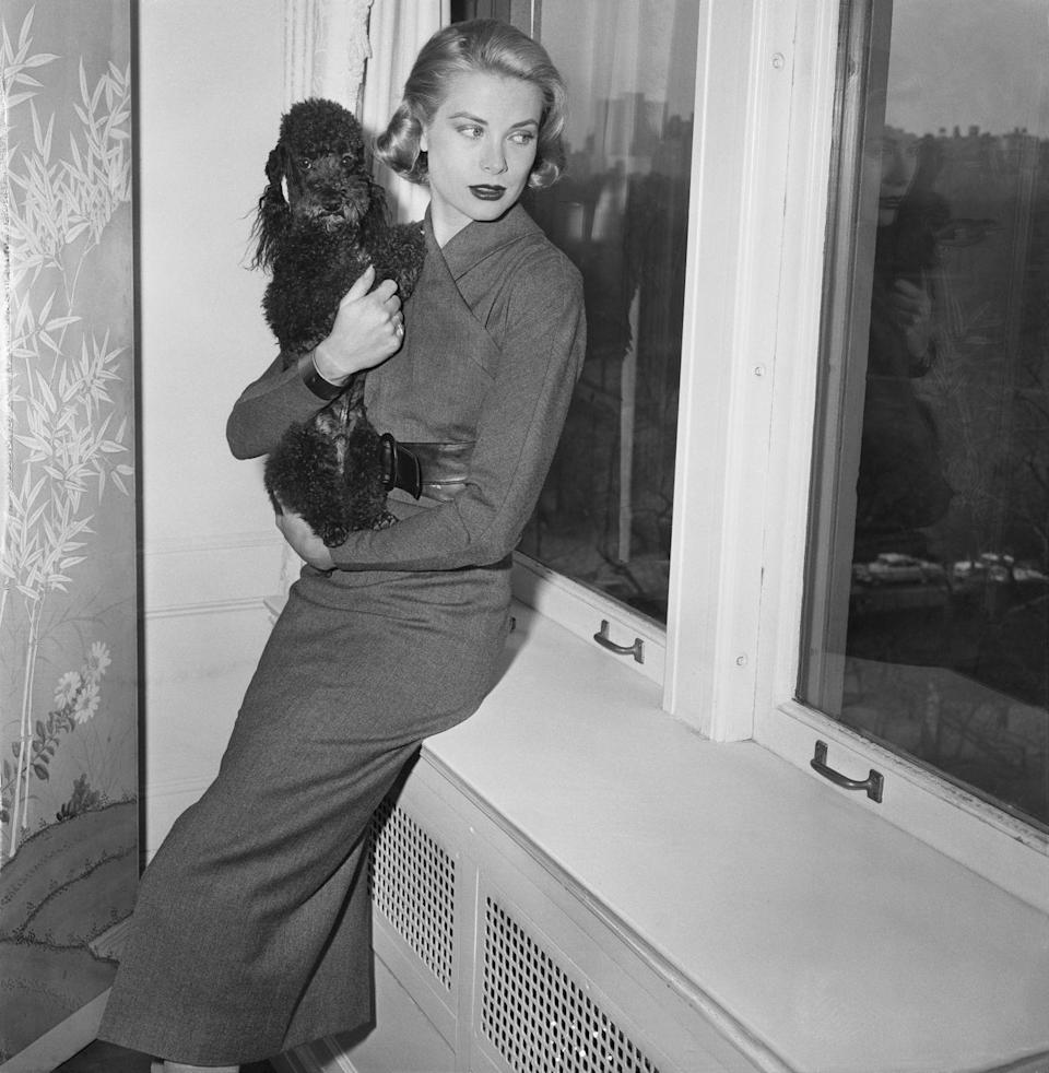 <p>The <em>Rear Window</em> star relaxes with her poodle on the windowsill of her Fifth Avenue apartment shortly before departing to Monaco before her nuptials to Prince Rainier, circa 1956.</p>