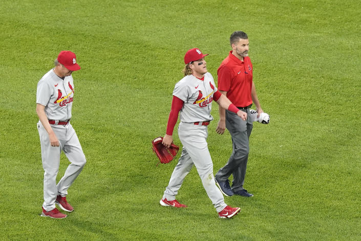St. Louis Cardinals' Harrison Bader, center, leaves the game with manager Mike Shildt, left, and a member of the training staff after Bader was unable to make a diving catch of a shallow fly ball by Chicago White Sox's Nick Madrigal during the third inning of an interleague baseball game Monday, May 24, 2021, in Chicago. (AP Photo/Charles Rex Arbogast)
