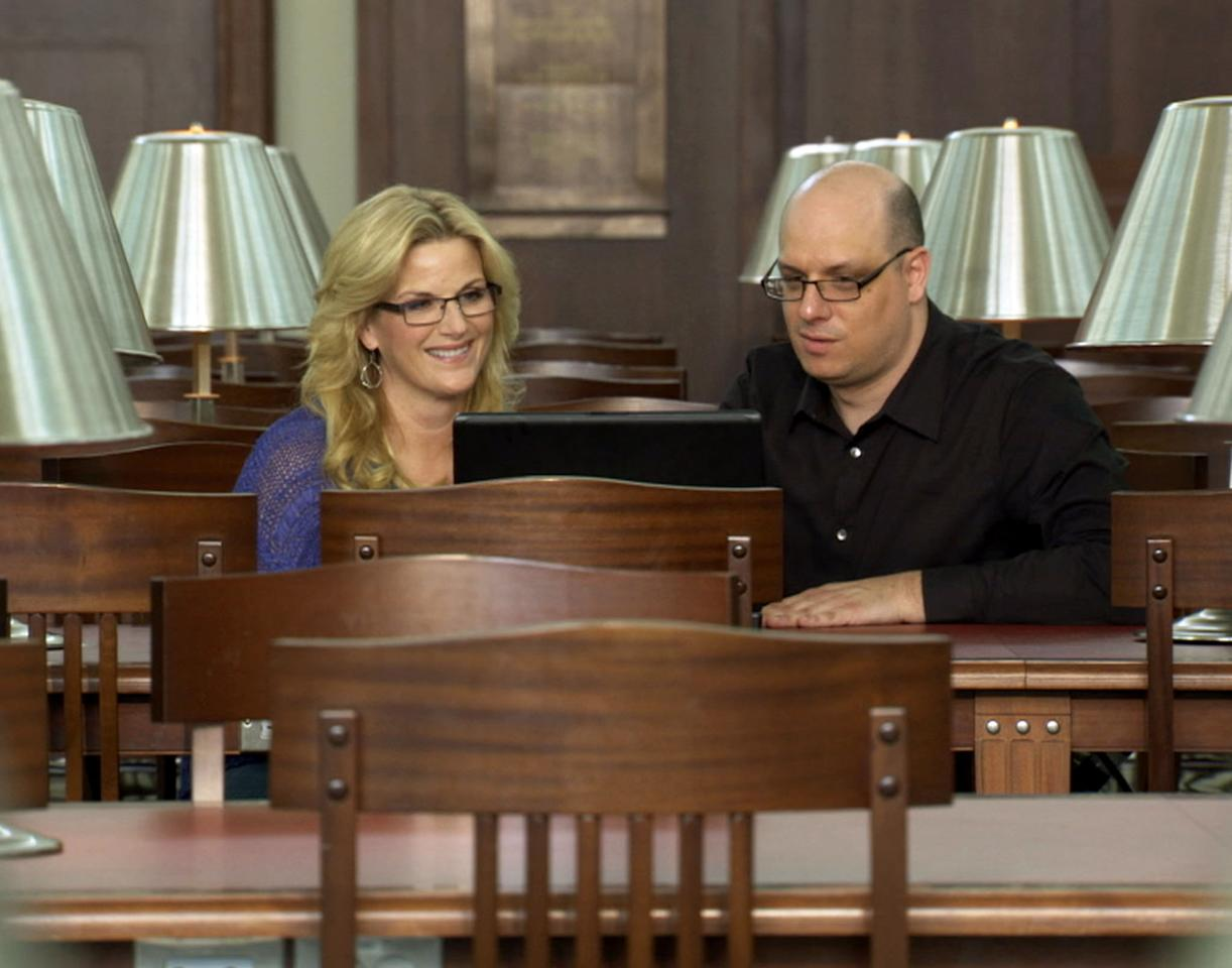 "Trisha Yearwood looks at a document with genealogist Kyle Betit at Nashville Public Library in TLC's ""Who Do You Think You Are?"""