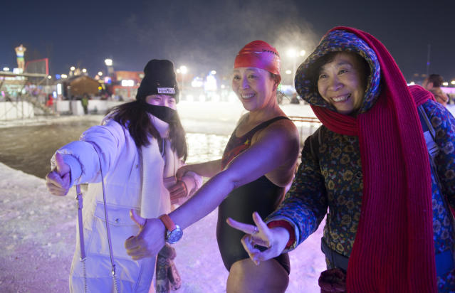<p>A winter swimmer takes a photo with tourists at Ice and Snow World park on Jan. 4 in Harbin, China. (Photo: Tao Zhang/Getty Images) </p>