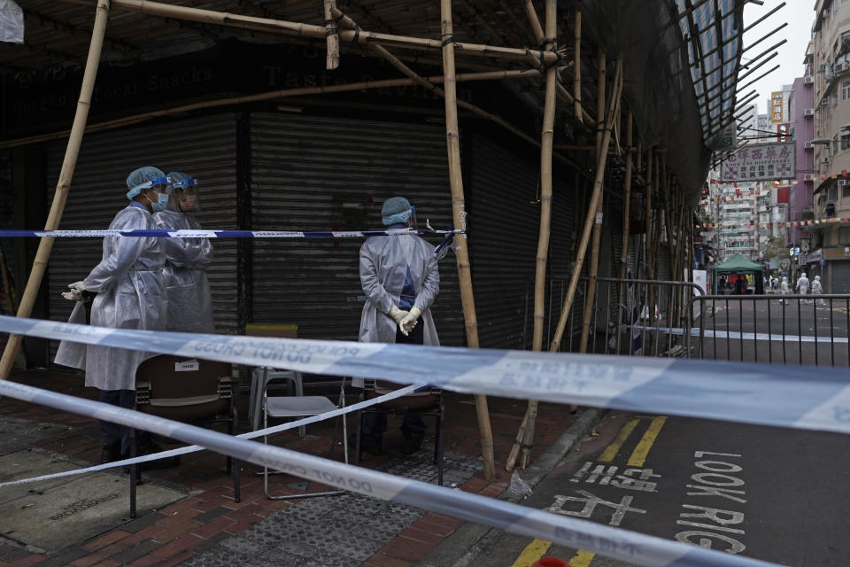 Government workers wearing personal protective equipment stand guard at the closed area in Jordan district, in Hong Kong, Sunday, Jan. 24, 2021. Thousands of Hong Kong residents were locked down Saturday in an unprecedented move to contain a worsening outbreak in the city, authorities said. (AP Photo/Vincent Yu)