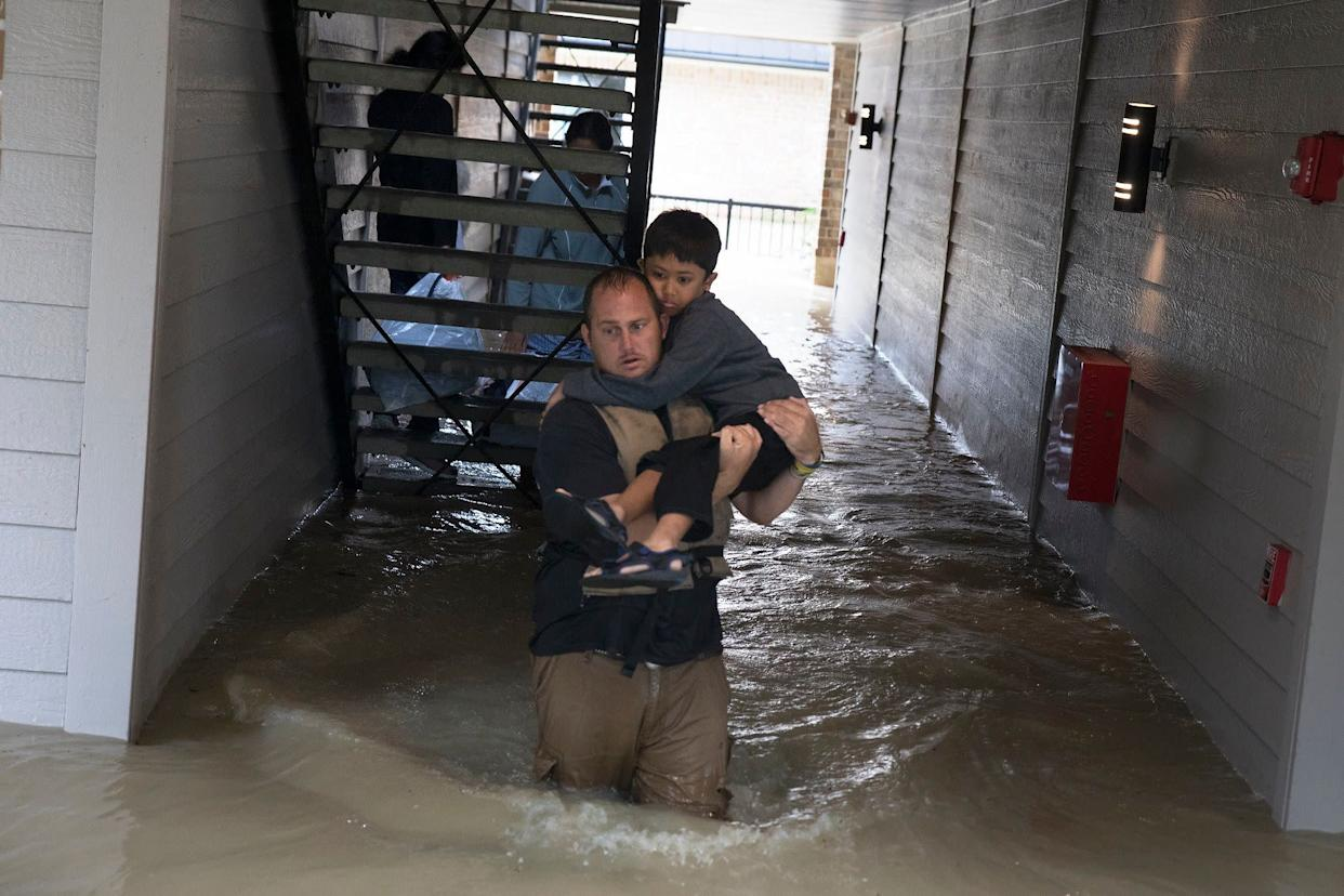 Volunteer Dustin Langley, who lives two hours north of Houston and came down with a friend to volunteer, helps a family to escape their flooded apartment in Kingwood.