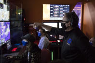 Boise State esports coach Doc Haskell talks to students in the control room during an esports match in Boise, Idaho, on Thursday, Mar. 4, 2021. Colleges and universities rushing to invest in the booming arena of varsity esports are overwhelmingly committing opportunities and scholarships to male players, according to data collected by The Associated Press. Boise State was among the more equal schools in the AP's survey, with 16 male players, five female players and three who identified as nonbinary.(AP Photo/Otto Kitsinger)