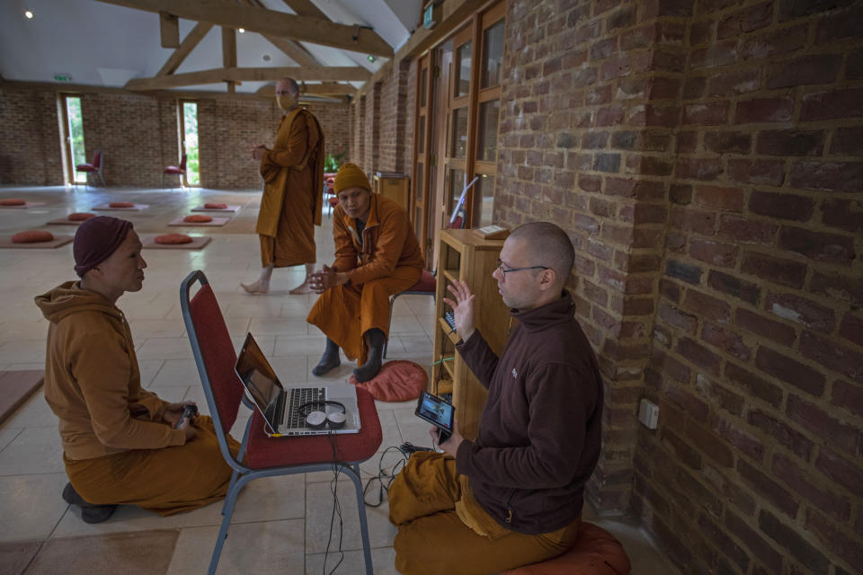 Monks Ajahn Kongrit, right, Tan Jalito, left, and Tan Narindo, center, discuss the logistics of live online streaming the Moon Day puja and precept ceremony to their community from Amvrati Buddhist Temple, which is currently closed to the public due to the coronavirus pandemic in Great Gaddesden, England, on Sunday, June 28, 2020. Spokesman Ajahn Dhammanando said the reopening of the temple as the United Kingdom emerges from coronavirus lockdowns will happen with the utmost caution. (AP Photo/Elizabeth Dalziel)