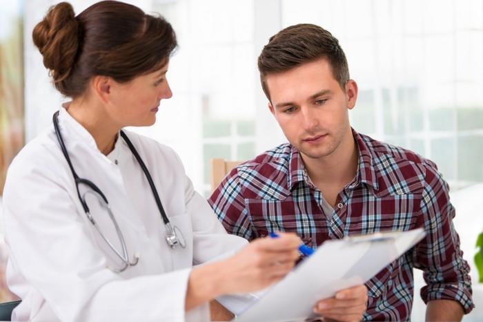Doctor reviewing chart with man