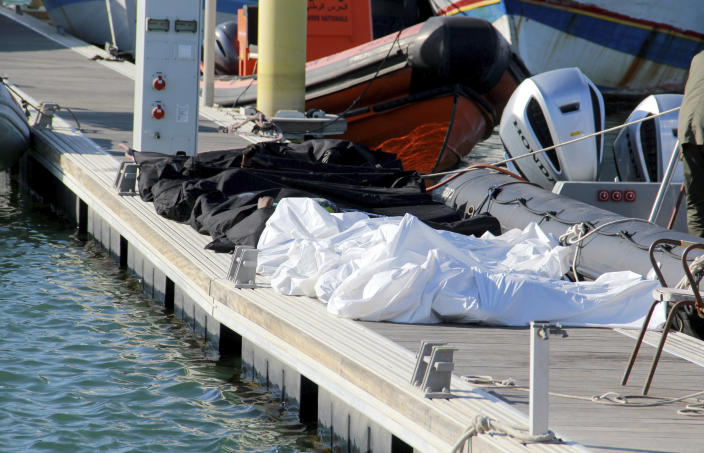 Covered dead bodies of migrants are pictured in the port of Sfax, central Tunisia, Thursday, Dec. 24, 2020. About 20 African migrants were found dead Thursday after their smuggling boat sank in the Mediterranean Sea while trying to reach Europe, Tunisian authorities said. Coast guard boats and local fishermen found and retrieved the bodies in the waters off the coastal city of Sfax in central Tunisia. (AP Photo/Houssem Zouari)