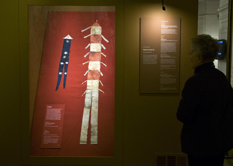 "A woman looks at a silk banner with floral appliquets, left, and a preyer banner, displayed in ""Dunhuang: Buddhist Art at the Gateway of the Silk Road,"" at the China Institute, in New York, Tuesday, April 24, 2013. (AP Photo/Richard Drew)"