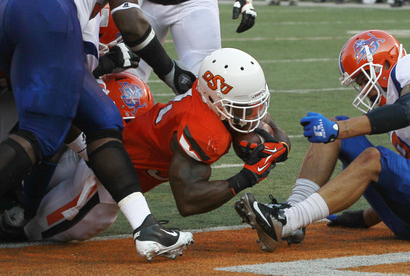 Oklahoma State running back Jeremy Smith, center, dives into the end zone for a touchdown against Savannah State in the first quarter of an NCAA college football game in Stillwater, Okla., Saturday, Sept. 1, 2012. Savannah State defensive back Vaughn Cornelia is at right. (AP Photo/Sue Ogrocki)
