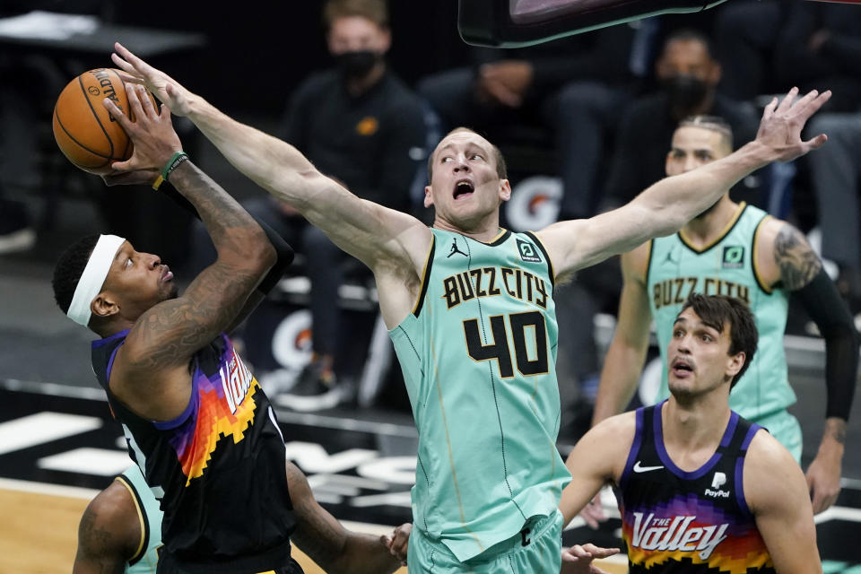 Phoenix Suns forward Torrey Craig shoots over Charlotte Hornets center Cody Zeller during the second half of an NBA basketball game on Sunday, March 28, 2021, in Charlotte, N.C. (AP Photo/Chris Carlson)