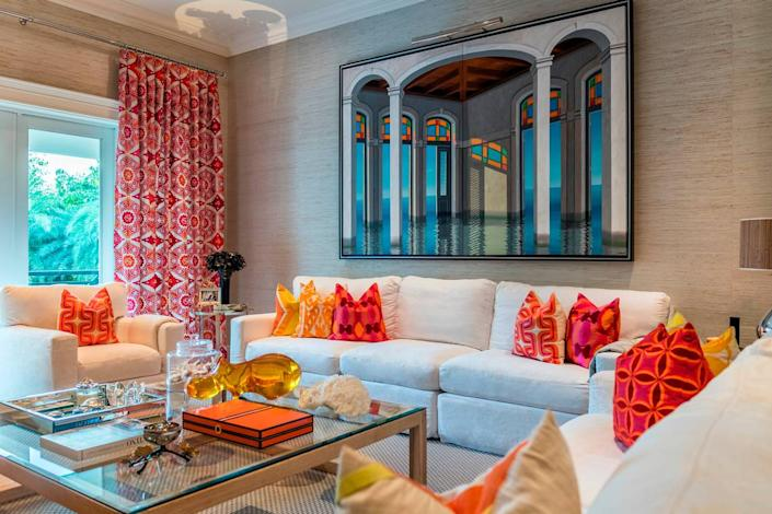 Above the sofa is a work by Humberto Calzada, with accent pillows by fashion designer Trina Turk, and a whimsical Lucite hippo by Jonathan Adler.