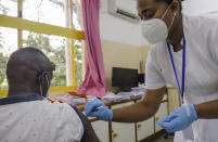 Khamis Juma, left, receives an injection of the 'Covishield'' coronavirus vaccine manufactured by the Serum Institute of India, from nurse Amelie Richmond, right, at a hospital in the capital Victoria, Mahe Island, Seychelles Wednesday, Feb. 24, 2021. The president of the Indian Ocean island nation of Seychelles says he hopes enough residents will soon be vaccinated against COVID-19 to stop the spread of the virus, hoping to achieve herd immunity by mid-March by vaccinating about 70% of the population. (AP Photo)