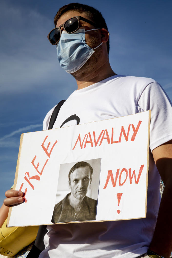 A protester holds a sign during a peaceful rally to speak up against political repressions, human rights violations and antidemocratic rule in Russia, during a demonstration in Geneva, Switzerland, Tuesday, June 15, 2021. Geneva is hosting a meeting between U.S. President Biden and Russian President Putin on June 16. A couple dozen supporters of Navalny, the jailed Russian opposition leader, staged a rally Tuesday on a sun-drenched Geneva square.(Magali Girardin/Keystone via AP)