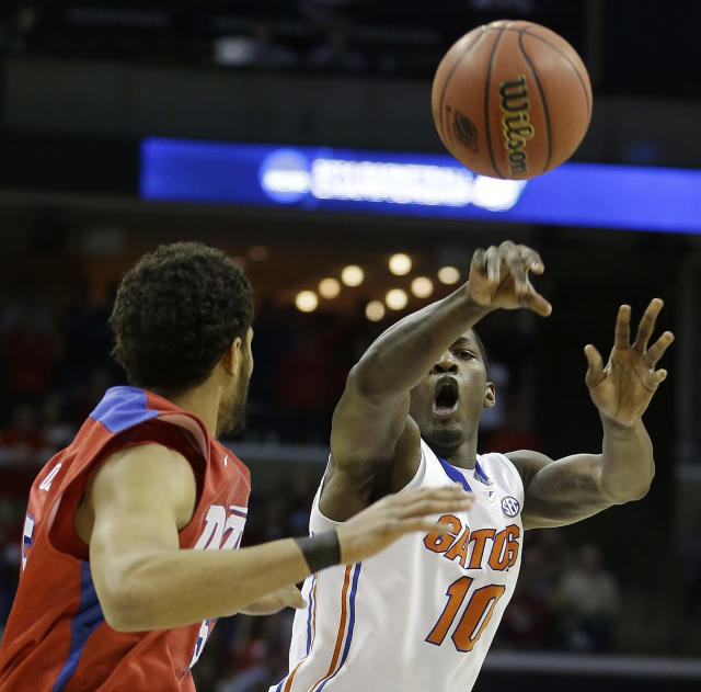 Florida forward Dorian Finney-Smith (10) passes the ball by Dayton forward Devin Oliver (5) during the first half in a regional final game at the NCAA college basketball tournament, Saturday, March 29, 2014, in Memphis, Tenn. (AP Photo/Mark Humphrey)