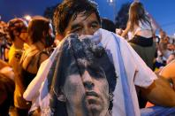 People mourn soccer legend Diego Maradona outside the morgue where his body is being held, in Buenos Aires