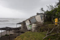 A journalist takes pictures of a damaged house that was damaged by winds brought on by Hurricane Grace, in Tecolutla, Veracruz State, Mexico, Saturday, Aug. 21, 2021. Grace hit Mexico's Gulf shore as a major Category 3 storm before weakening on Saturday, drenching coastal and inland areas in its second landfall in the country in two days. (AP Photo/Felix Marquez)