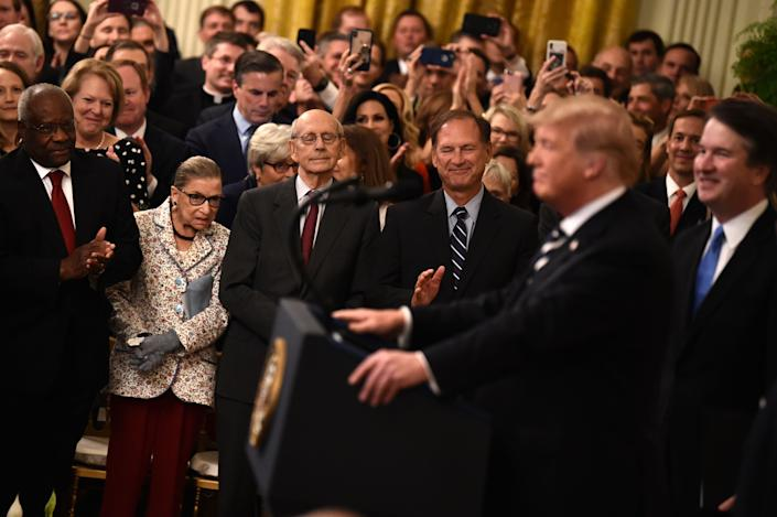 From left: Supreme Court Associate Justices Clarence Thomas, Ruth Bader Ginsburg, Stephen Breyer and Samuel Alito listen as President Trump speaks during the swearing-in ceremony of Brett Kavanaugh, far right. (Photo: Brendan Smialowski/AFP/Getty Images)