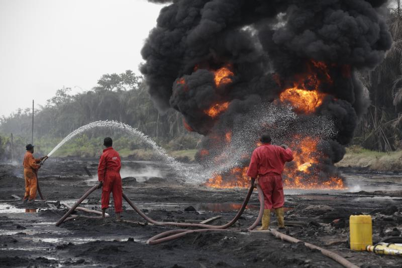 Fire fighters try to contain flames from a burning oil pipeline in Ijeododo outskirt of Lagos, Nigeria Thursday, Dec. 20, 2012. The oil pipeline belonging to Nigeria National Petroleum Cooperation exploded near Nigeria's largest city as thieves tried to siphon oil from it Monday. (AP Photo/Sunday Alamba)