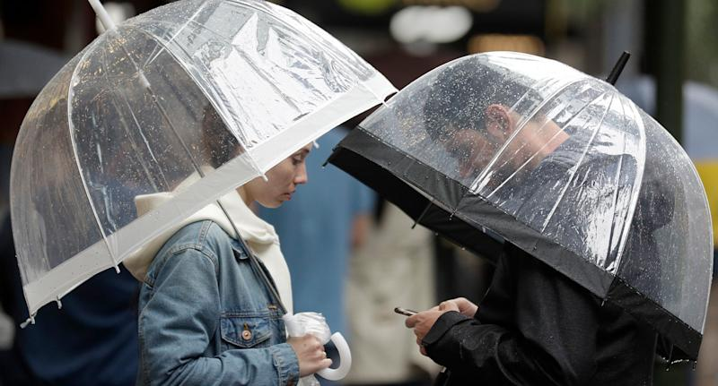 A couple shelter under an umbrellas as rain falls in Sydney. Source: AAP