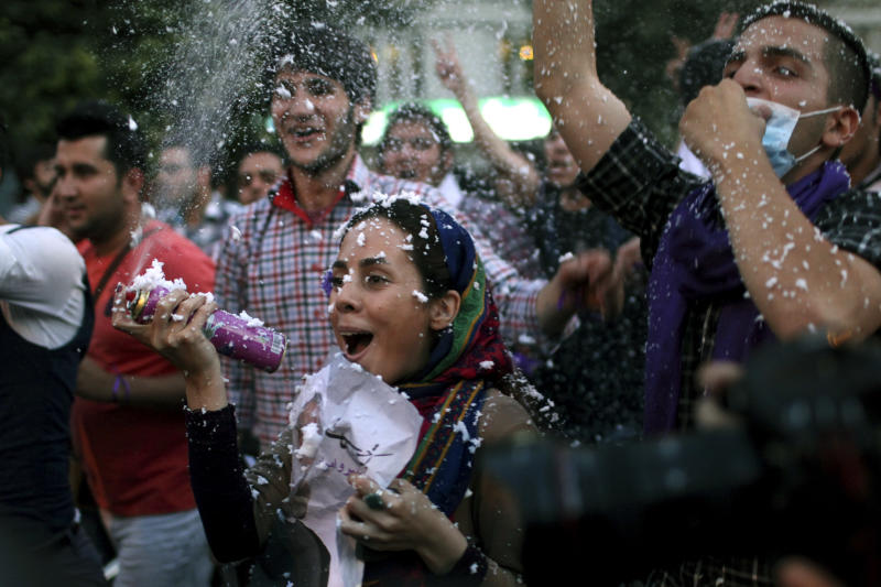 Supporters of Iranian presidential candidate Hasan Rowhani attend a celebration gathering following his victory in Tehran, Iran, Saturday, June 15, 2013. Wild celebrations broke out on Tehran streets that were battlefields four years ago as reformist-backed Rowhani capped a stunning surge to claim Iran's presidency on Saturday, throwing open the political order after relentless crackdowns by hard-liners to consolidate and safeguard their grip on power. (AP Photo/Ebrahim Noroozi)