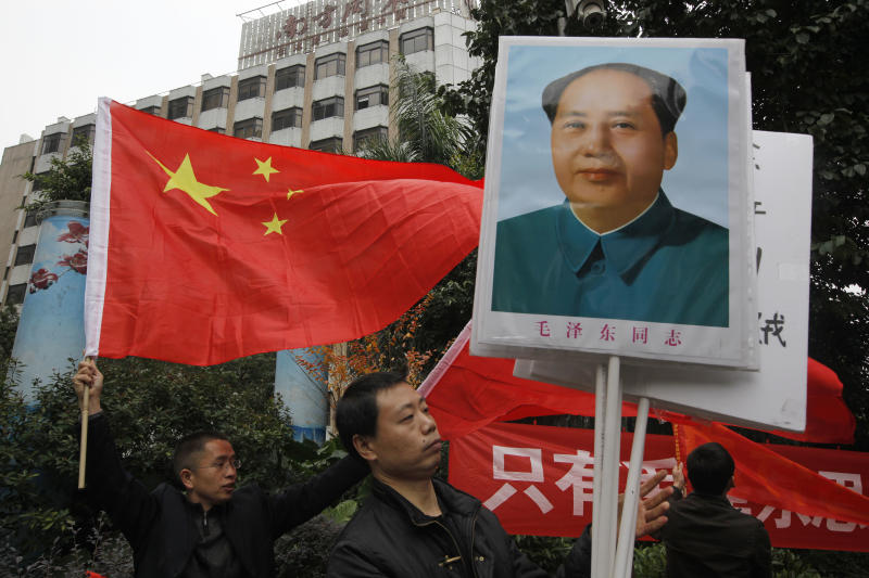 In this Wednesday, Jan. 9, 2013 photo, leftists stage a counter-protest with portraits of former Chinese leader Mao Zedong against supporters of the Southern Weekly outside the headquarters of the newspaper in Guangzhou, Guangdong province, China. China's new Communist Party leaders want to appear more open, but they're not about to give up control of the media. That's the lesson of a dustup involving the influential newspaper whose staff briefly rebelled against especially heavy-handed censorship. (AP Photo/Vincent Yu)