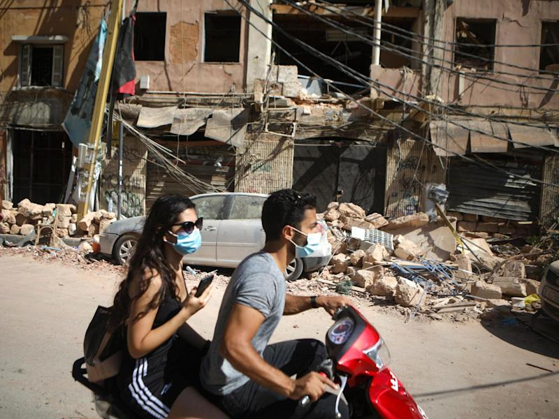 A Lebanese couple drive past the debris of a building following an explosion at Beirut's port: PATRICK BAZ/AFP via Getty Images