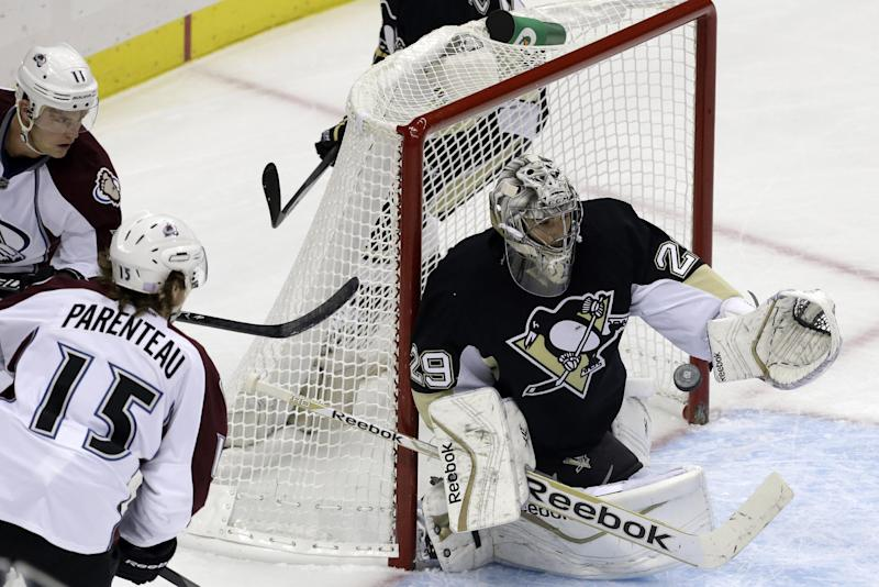 Pittsburgh Penguins goalie Marc-Andre Fleury (29) gloves the puck before Colorado Avalanche's P.A. Parenteau (15) and Jamie McGinn (11) can get a stick on it in the first period of an NHL hockey game in Pittsburgh Monday, Oct. 21, 2013. (AP Photo/Gene J. Puskar)