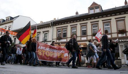 "Supporters of the far-right National Democratic Party (NPD) hold a banner reading ""Stop the asylum abuse"" during a march in Riesa, Germany, September 9, 2015. REUTERS/Fabrizio Bensch"