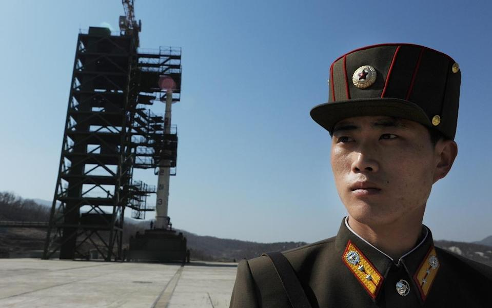 A North Korean soldier stands guard in front of an Unha-3 rocket at the Sohae Satellite Launch Station in Tongchang-Ri on April 8, 2012 (AFP Photo/Pedro Ugarte)