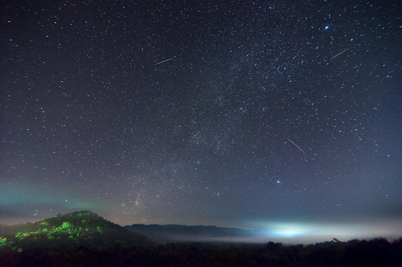 The Milky Way during the Leonid meteor shower in the night sky with the mist on hill, Long Exposure, Lampang Thailand.