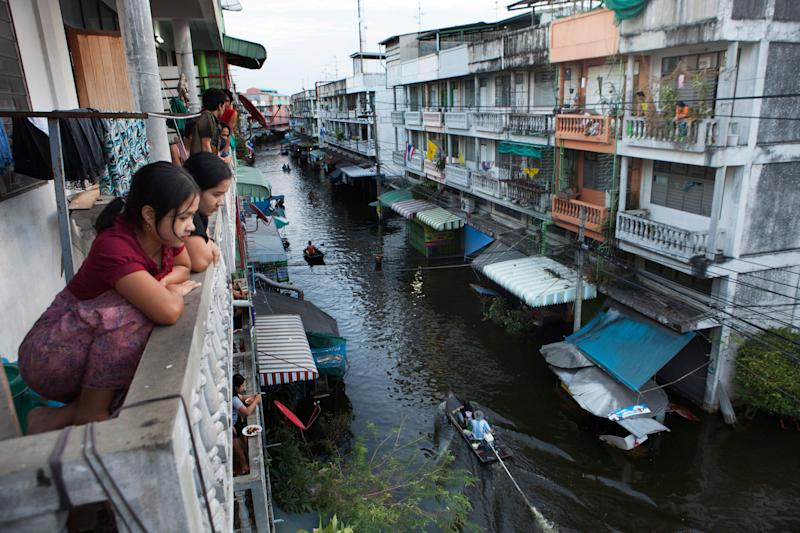 Bangkok residents look down at a flooded street where boats have become the main mode of transport in 2012. (Photo: Gideon Mendel/Getty Images)