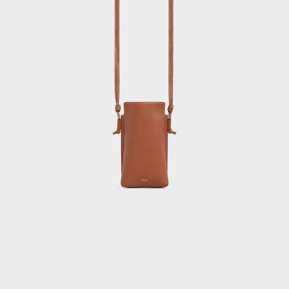 "<p><strong>Celine</strong></p><p>celine.com</p><p><strong>$650.00</strong></p><p><a href=""https://www.celine.com/en-us/celine-shop-women/small-leather-goods/tech-accessories/phone-pouch-in-smooth-lambskin-10F683CLO.04LU.html"" rel=""nofollow noopener"" target=""_blank"" data-ylk=""slk:Shop it"" class=""link rapid-noclick-resp"">Shop it</a></p><p>Keep things classic with a tan phone pouch. Pair this luxe accessory with a crisp white button-down and jeans for a chic off-duty look. </p>"